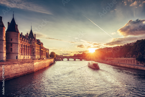 Garden Poster Paris Beautiful skyline of Paris, France, with Conciergerie, Pont Neuf and cruise boat at sunset. Colourful travel background. Romantic cityscape.