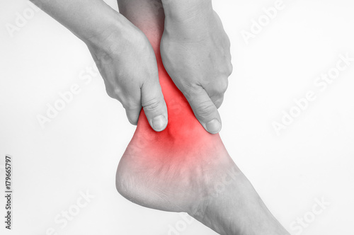 Photo Woman with ankle pain holding her aching leg