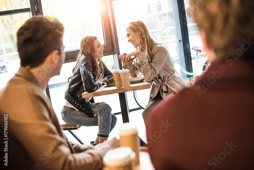 Canvas Print men looking at girls at adjacent table