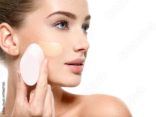 Girl applies  tonal foundation  on the face use sponge Fototapet