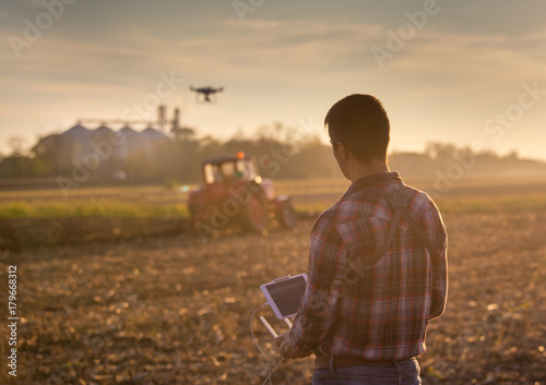 Fototapeta Farmer navigating drone above farmland obraz