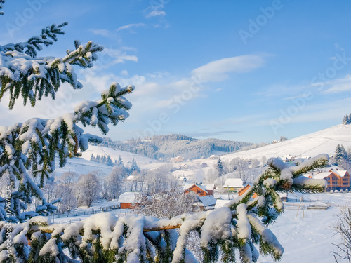 Fototapety, obrazy: Mountain village with spruce branches on foreground in winter