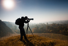 Silhouette Of Photographer Taking Landscape Photos In Morning.