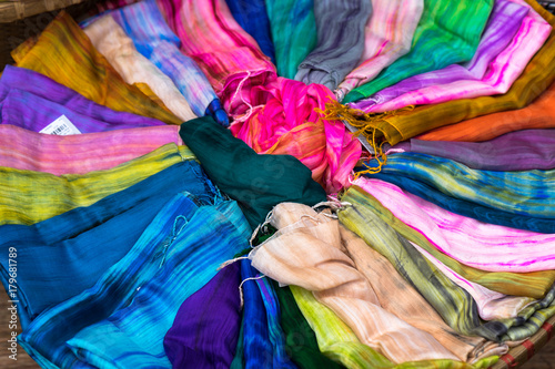 Fotoposter Paradijsvogel bloem Stack of colourful silk scarfs