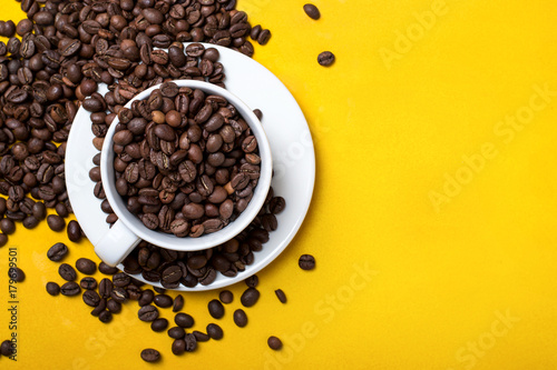 Coffee cup with beans on yellow background. Top view with copy space