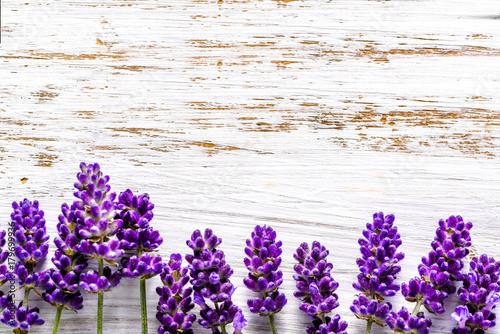Valokuva  Lavender flowers frame on white wooden background, overhead