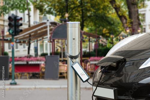 Plakat Samochód elektryczny jest ładowany na parkingu w pobliżu kawiarni ulicznej