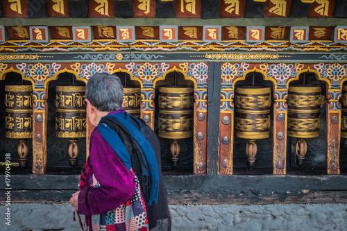 Photo Old woman spinning prayer wheels in Thimphu, Bhutan
