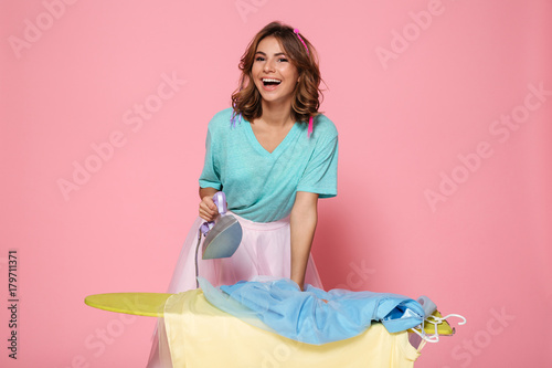Portrait of a happy young girl ironing her clothes Fototapeta