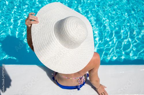 Obraz na dibondzie (fotoboard) Młoda kobieta siedzi przy krawędzi basenu