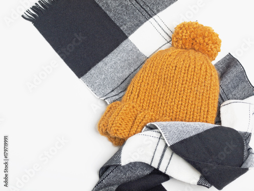 68999b26ca7 Mustard knit beanie hat with big pom pom and black and white checked scarf  isolated on