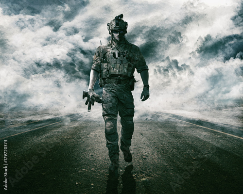 Fotografía  Army soldier moving towards camera on cloudscape background