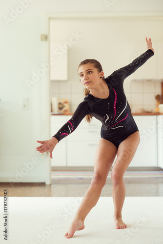 Tuinposter Gymnastiek Young pretty girl has training gymnastics at home in white interior