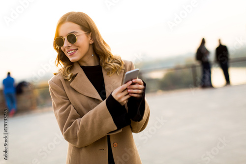 Fotografija Young woman with eyeglasses with mobile phone outdoor