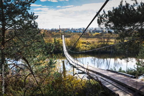 Fototapeta Bridge over the river and the autumn nature around