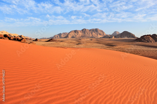 Wadi Rum desert in Jordan. Big area with smooth untouched red sand and mountains at the background and blue sky with clouds.
