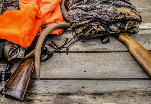Foto op Canvas Jacht Deer Hunting Background. Hunting rifles, scope, antlers, bullets, and hunting apparel on a rustic wooden background with copy space.