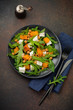 Vegetarian salad with arugula, baked pumpkin, herbs and seasonings, feta cheese, chickpeas and olive oil in a black ceramic plate on a dark concrete or stone background. Selective focus.