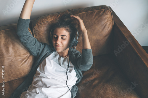 Beautiful young happy woman listening to music from headphones with pleasure at coworking office, lying on sofa and resting. - 179755188