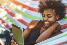 Cute Cheerful Teenage Brazilian Female With African Hair Is Laying In Colorful Striped Hammock Located In Public Park On Warm Sunny Day And Smiling While Reading Funny Memes On Her Digital Tablet