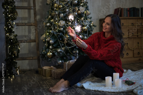Photo  A young barefoot girl is sitting near the New Year tree in the room with Christmas decoration and lights
