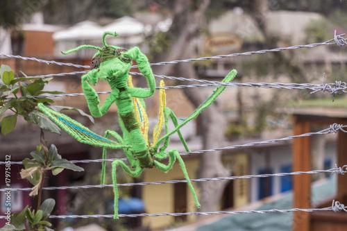 Photo mantis religiosa hecha en lana enganchada en un alambre de puas
