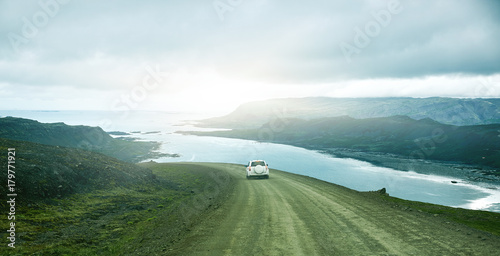 Poster Kaki Travel to Iceland. plot of road in a dark cloudy mountain landscape. focus on the road