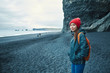 woman traveler with small orange backpack walking on black sand beach, southern Iceland.