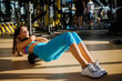 Leinwanddruck Bild -  Beautiful active sporty young woman doing pilates on the floor with a foam roller in the sunny gym.