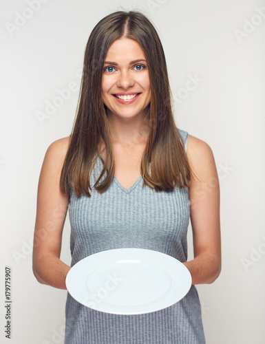 Woman holding white plate. Smiling girl waitress