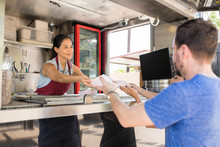 Woman In Food Truck Selling Hot Dogs