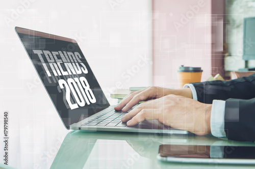 "Fotografía  Hand of Businessman typing "" trends 2018"" on laptop screen with smartphone and coffee cup in home office or co working space"