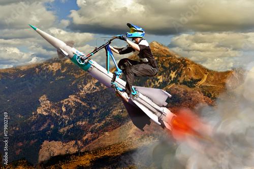Fototapeta Konceptualny wizerunek rowerzysta lata w górę na rakiecie