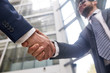 Firm handshake of business partners, interior of modern office lobby on background, close-up shot