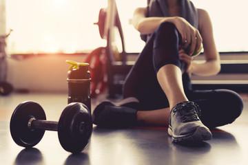 Žena vježba vježbanje u teretani fitnes razbijanje opuštanje držanje voća jabuka nakon treninga sport s bučicama i proteinskim shake bočicama zdrav životni stil bodybuilding, sportaš graditelj mišića stil života