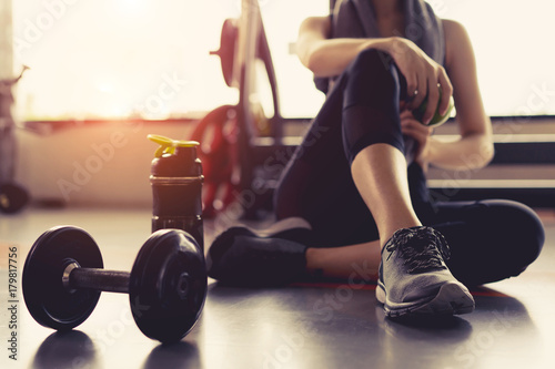 Slika na platnu Woman exercise workout in gym fitness breaking relax holding apple fruit after training sport with dumbbell and protein shake bottle healthy lifestyle bodybuilding, Athlete builder muscles lifestyle