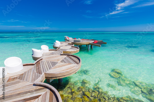 Stampa su Tela Tropical beach scene with loungers and blue sea and blue sky