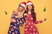 New Year. Young Woman With Christmas Props, Holiday Fashion Santa Hat Having Fun Happy. Blowing Lips Make Air Kiss. Playful Sisters Friends, Stylish Fashion Red Xmas Dress On Yellow. Vintage Christmas