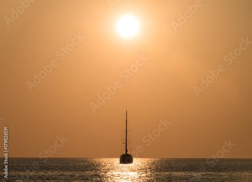 Plakat Jacht w morzu o zachodzie słońca.