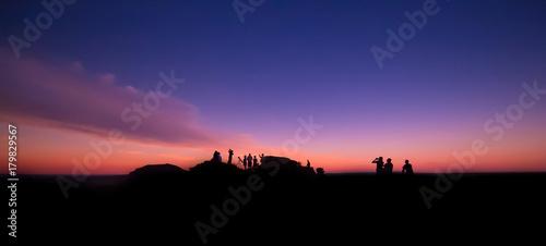 Sylwetki ludzi siedzących na górze i obserwujących słońce podczas Wielkiego Amerykańskiego Zaćmienia Słońca. 21 sierpnia 2017 r. Wyoming, USA.