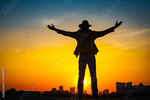 Canvas Prints Military Traveler silhouette with a backpack and cowboy hat stand on hill top. City in the background. Sun sets over horizon. Man looks ahead, raise his arms up. Travel, holidays, advanture, success concept.