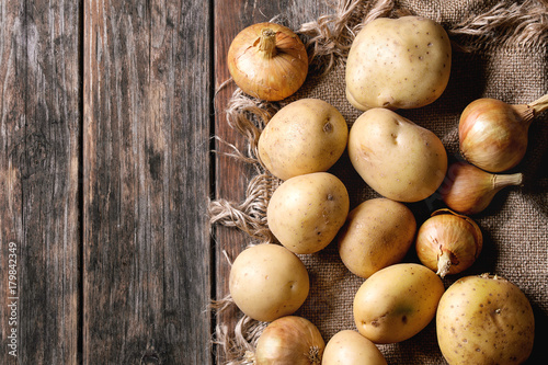 Raw whole washed organic potatoes, onion and garlic on sackcloth over old wooden plank background. Top view with space. Close up