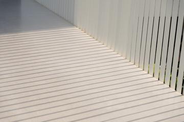 The shadow shining down on the floor of walkway.