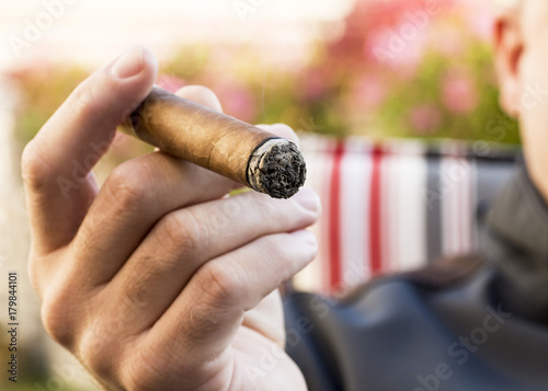 Fotografia  Detail of the hand of a smoking man holding a burning cigar with a blurred backg