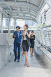 Professional business team using smartphone talk business project while walking forward confidently in cityscape background