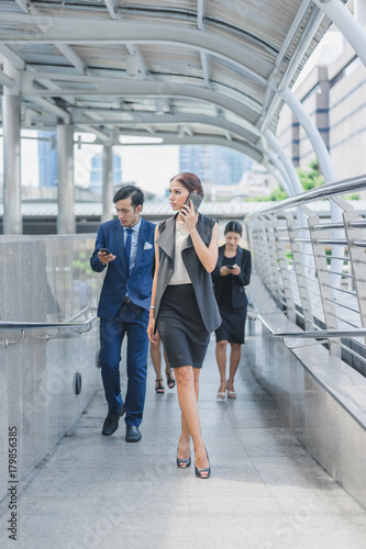 Fototapeta Professional business team using smartphone talk business project while walking forward confidently in cityscape background obraz na płótnie