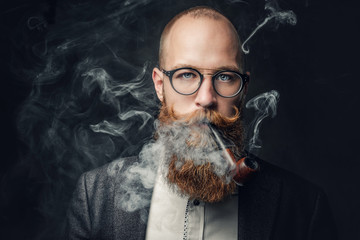 A man smoking pipe over gre...
