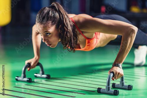 Zdjęcie XXL Kobieta robi pompki na siłowni