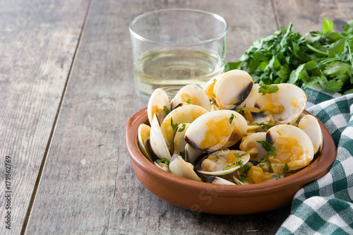 Clams with marinera sauce.Almejas a la marinera. Spanish recipe on wooden table