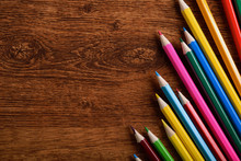 Colored Crayons Background. Many Different Colored Pencils On Old Vintage Wooden Background